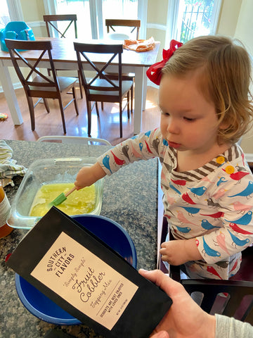 toddler making Southern City Flavors cobbler from Batch