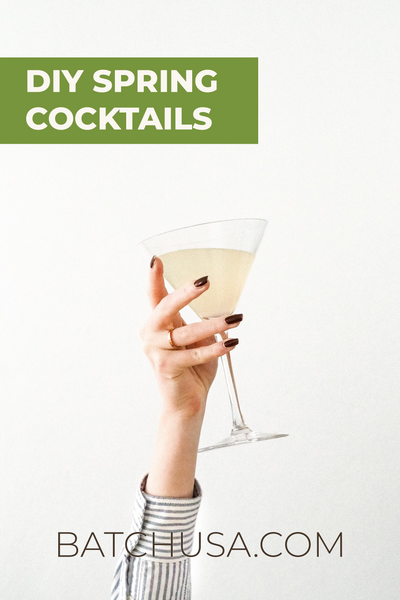 """DIY Spring Cocktails, BatchUSA.com"" Woman's hand holding margarita glass with cocktail inside on white background 
