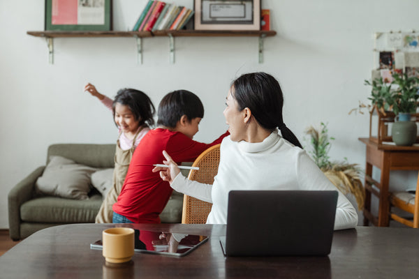 Mom works on laptop with children playing