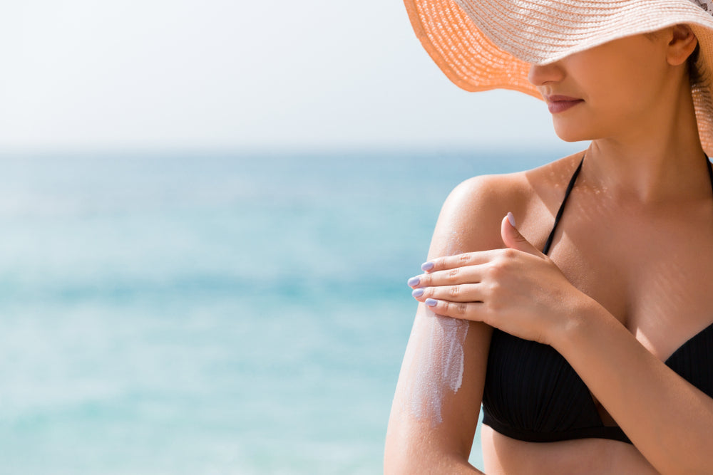 woman at beach applying sunscreen to arm