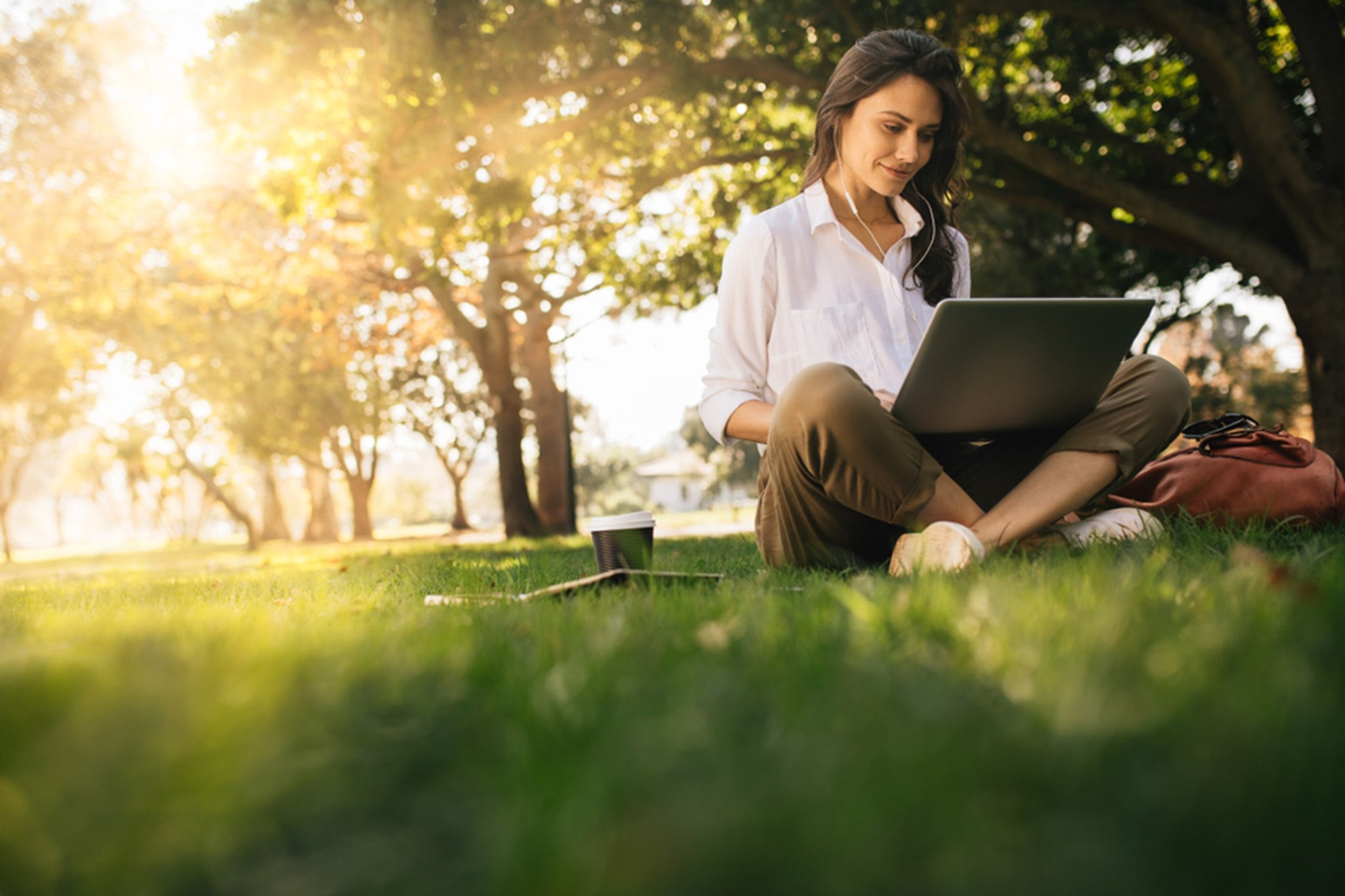 woman with laptop sitting outdside