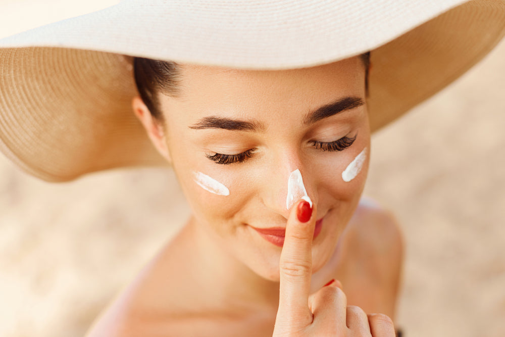 Woman in tan sun hat applying sunscreen to her face