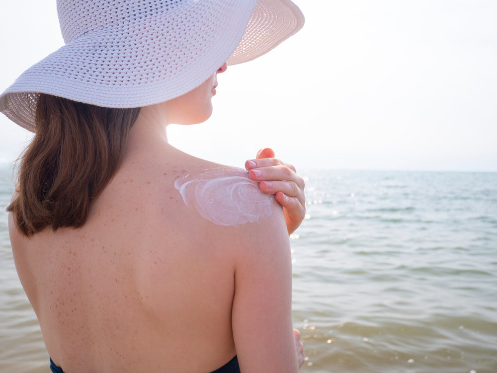 woman in white sun hat using waterproof sunscreen on her shoulder to avoid the need for home remedies for sunburn skin