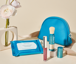 Hydrating Cleaning Coths, Total Protection Brush SPF 50 with cap off, and Lip Shine in Plume shade in front of a saffiano leather bag next to a flower in a vase