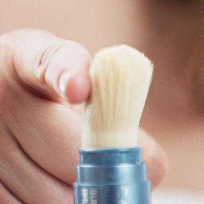 hand flicking the Sunforgettable®  Brush-on Shield SPF30 on the table