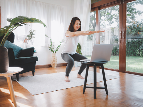 woman smiling in her living room exercising and looking at her laptop online class