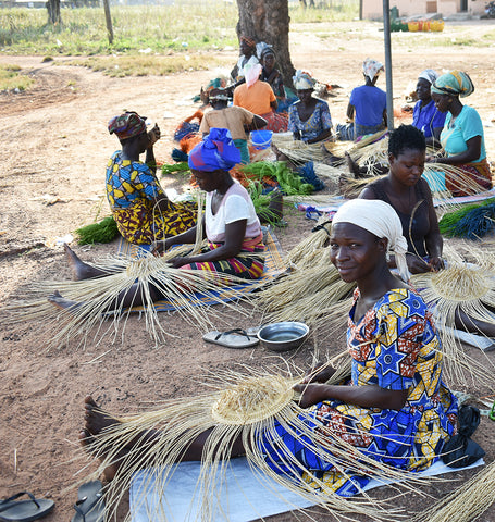 Community of weavers, working under a tree to weave fair trade Bolga Baskets, in the area near Bolgatanga, Ghana