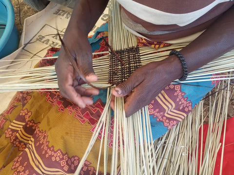 Binga basket artisan image, shows hands expertly weaving palm leaves and twigs.