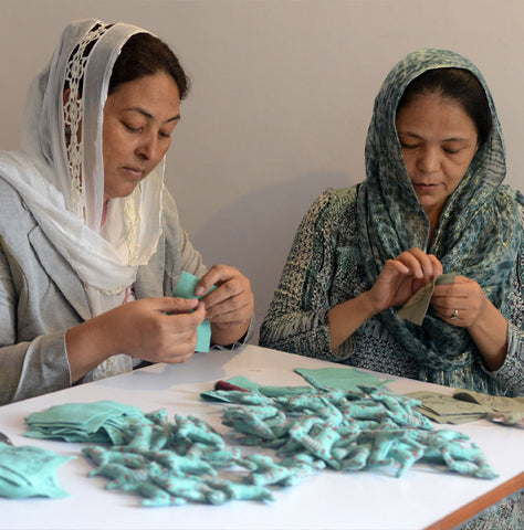 Image shows artisans handcrafting Snow Leopard ornaments.
