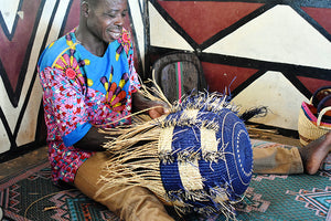 Ghanaian weaver has nearly completed this blue and natural bolga basket