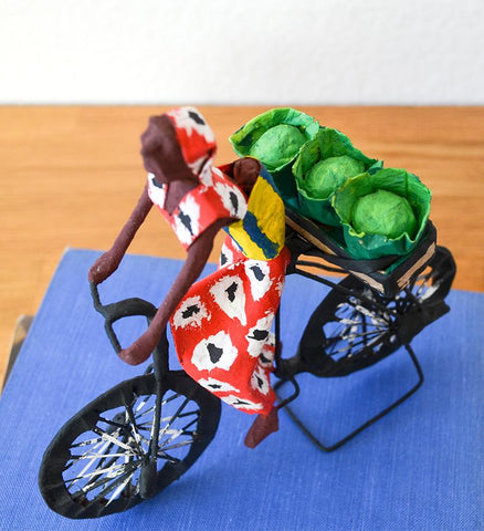 Detail image of Zambian woman, wearing baby, bicycling with cabbages. Folk art made in Zambia.
