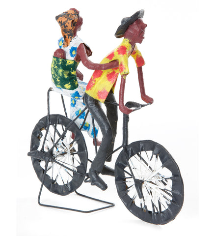 Bicycle art, Zambian papier-mache of a father, mother, and swaddled baby riding on a bike, wearing colorful handpainted clothes