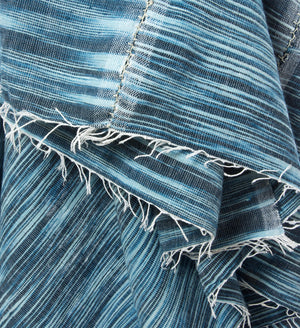 Close up photo of variegated dark blue textile with white fringe and center seam