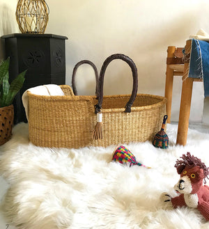 Handwoven bassinet basket in a baby's nursery, with sheepskin rug and stuffed animal. Neutral nursery decor. African basket.