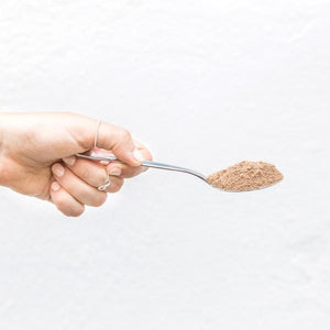 lady holding silver spoon of your superfoods energy bomb blend