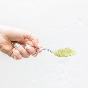 lady holding silver spoon of your superfoods power matcha blend