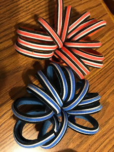 14 orange, black and white grap spirit bracelets and , 13 blue, white, and black grap spirit bracelets are pictured to show off your team spirit. easy to make with just two components. choose your colors and start creating team spirit and cash!