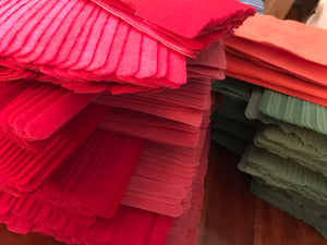 stacks of 100's of red, green and orange grap is pictured. Grap is double-sided hook and loop used to craft, organize and problem-solve in the home, garage,  RV, boat and craft room! Choose your color and start crafting!
