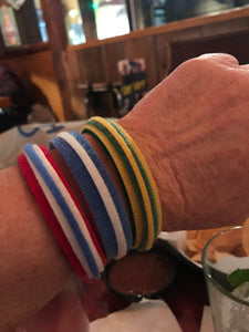 3 Spirit Bracelets made with Grap are pictured. One is green and yellow, one is blue and white, and one is red, white and blue. Grap is double-sided hook and loop used to craft, organize, and problem-solve in the home, garage, RV, boat and garage.