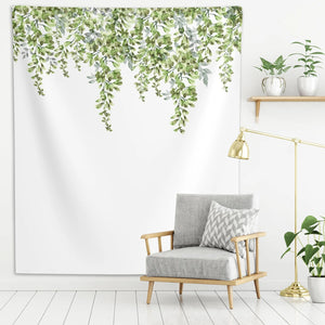 Green leaf wall tapestry, hanged on a white wall, above a gray couch