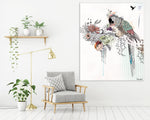 Large canvas painting of colorful parrot in the jungle, hanged on a white wall, above gray couch