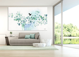 Large watercolor art of turquoise leaves, above a gray sofa