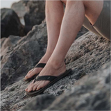 MAN'S FEET WITH FLIP FLOPS ON, SITTING ON A ROCK