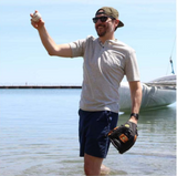 BRAD STANDING IN THE WATER, HOLDING A MITT AND THROWING A BASEBALL
