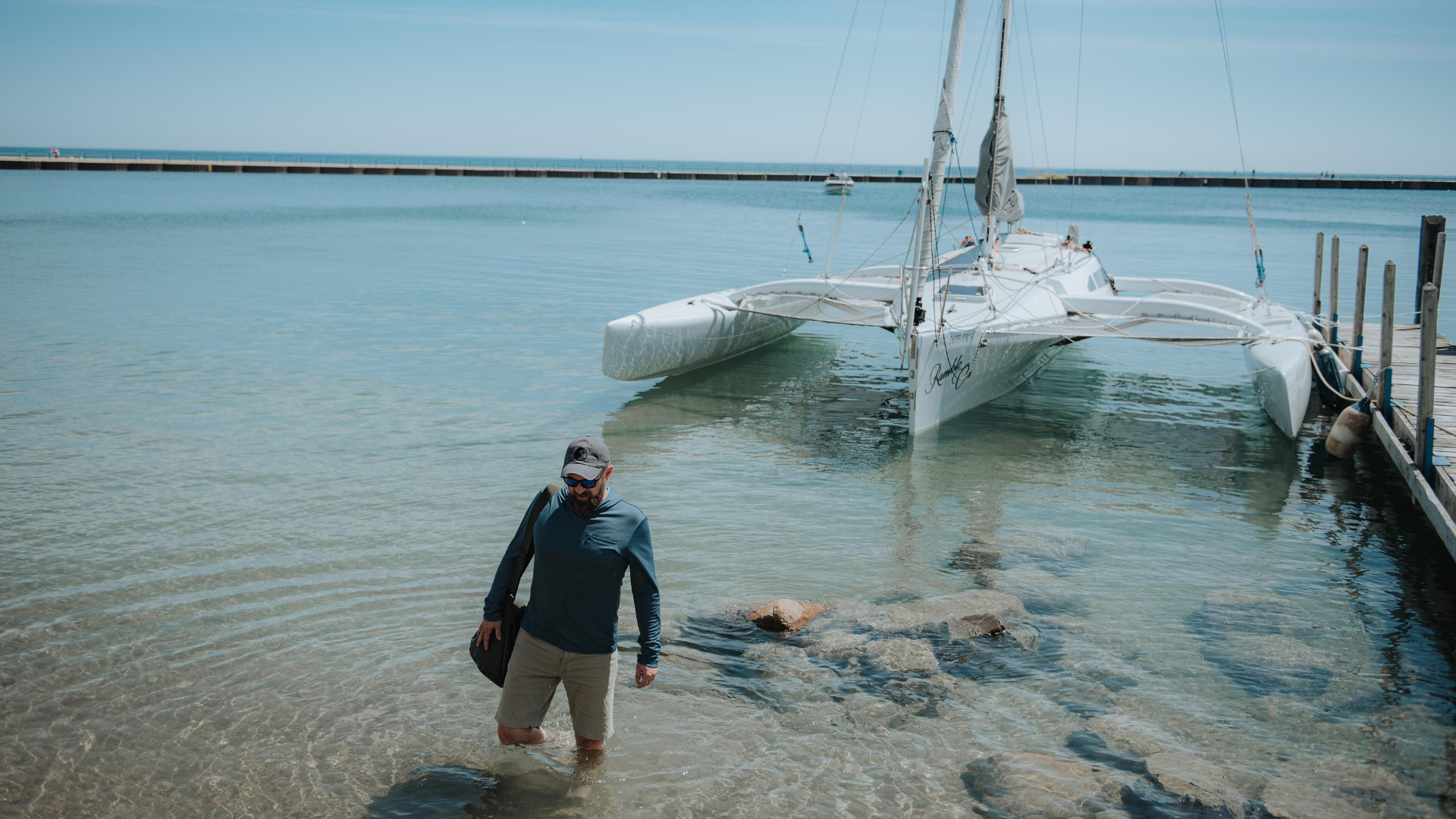 man walking through the water in front of a boat, wearing muskox shirt