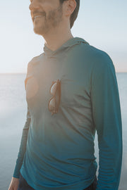 Performance Sun Hoodie in Marine Blue. The Charleston Performance Hoodie is a cooling shirt and performance base layer by MuskOx Men's Outdoor Apparel. Designed for outdoors, this sun shirt is constructed with UV blocking, moisture wicking, quick drying breathable lightweight fabric, and comes with thumbholes, chest pocket and a bungee sunglass bungee loop.