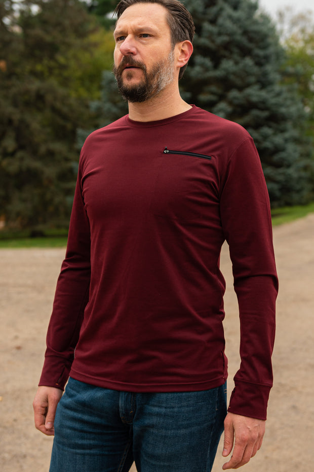Men's Outdoor Base Layer in Burgundy. Our Foundation Quick Dry base layer is men's performance activewear that is breathable, and moisture wicking. It is built with super soft breathable jersey that keeps you dry during your outdoor adventures. This cooling long sleeve base layer comes equipped with thumbholes and a chest pocket.