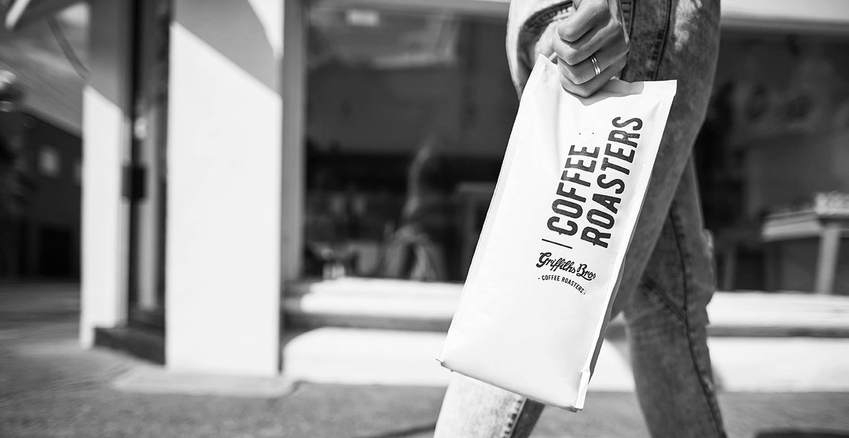 Griffiths Bros. Coffee Roasters. Girl holding bag of coffee walking past a cafe.