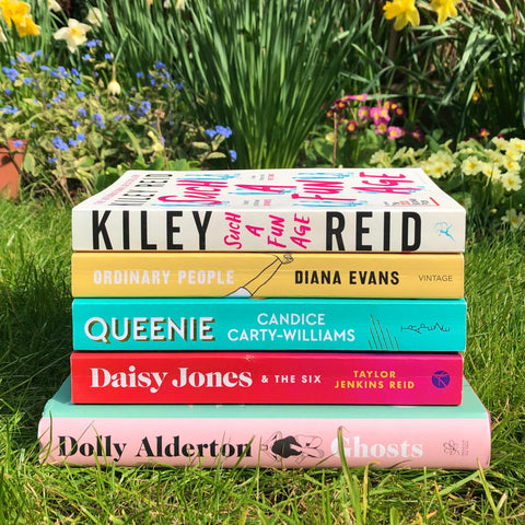 A stack of books from top to bottom: Such a Fun Age, Ordinary People, Queenie, Daisy Jones & The Six, Ghosts