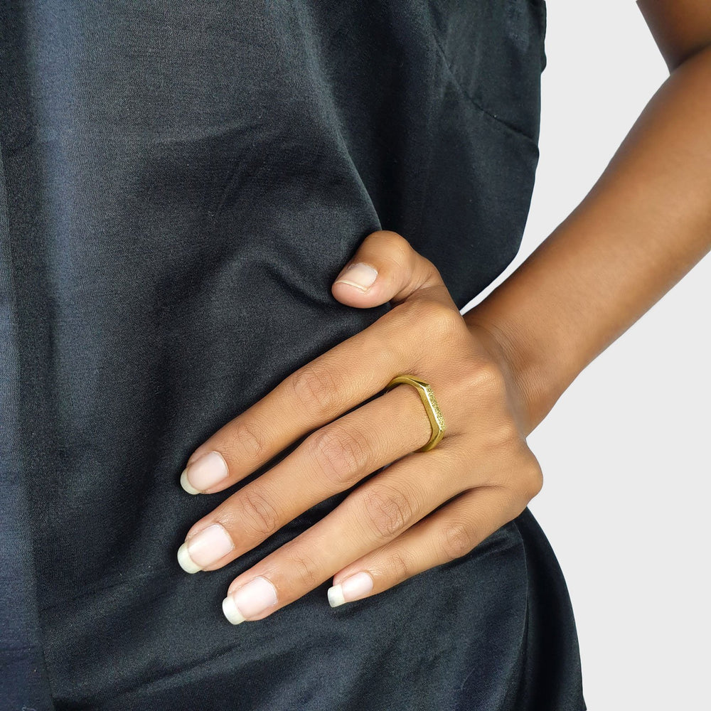 Brass gold color ring with flat and hammered front surface on model