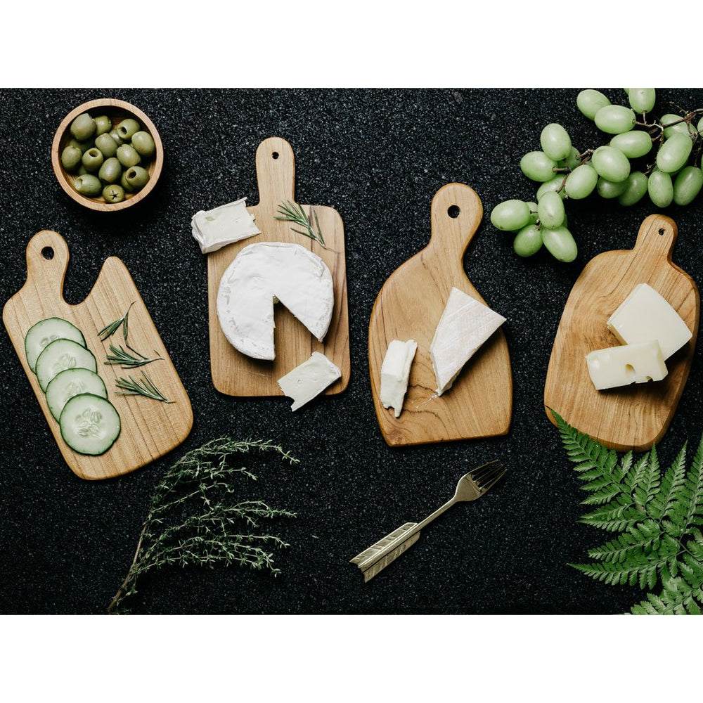 Set of Wooden cheese boards in 4 different shapes made of teak with food