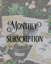Words 'Monthly Subscription' with sample box booklet, glass jar and plant, and tea in the background