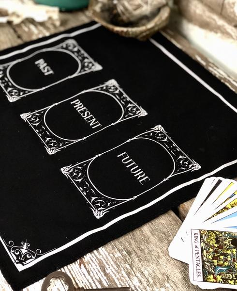 Photo of three card tarot cloth. Black with white lettering.