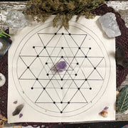 Overhead shot of a tan geometric grid cloth with a amethyst tower in the center.