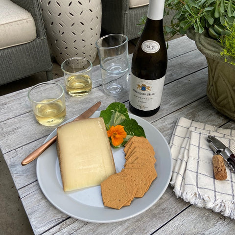 Dinner plate with wedge of cheese, crackers, and orange flower next to white wine in glasses and stack of white cloth napkins