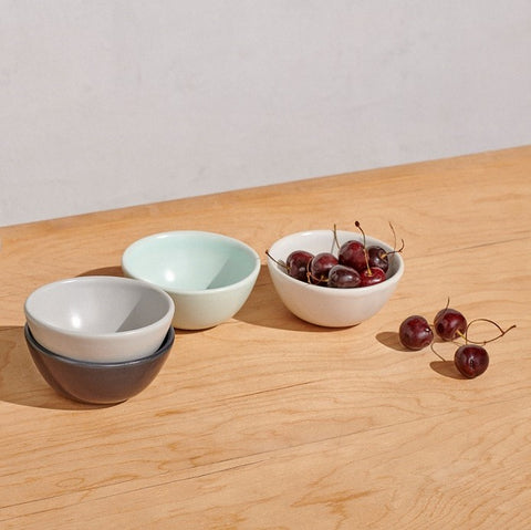 Four mini bowls in 4 colors on table with cherries
