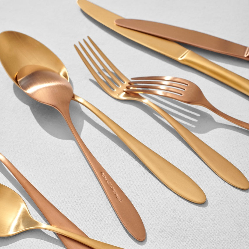 Mix of gold and copper flatware pieces