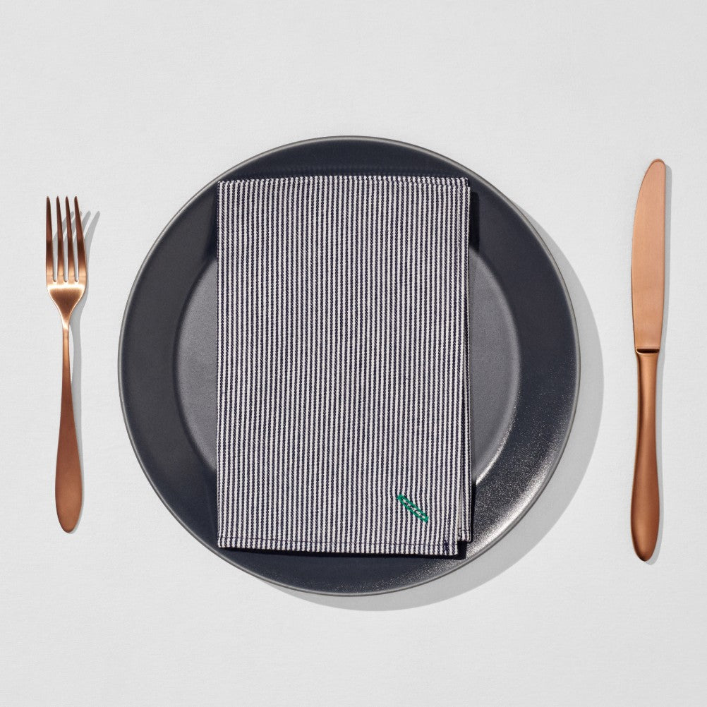 Copper knife and fork next to dinner plate and striped napkin