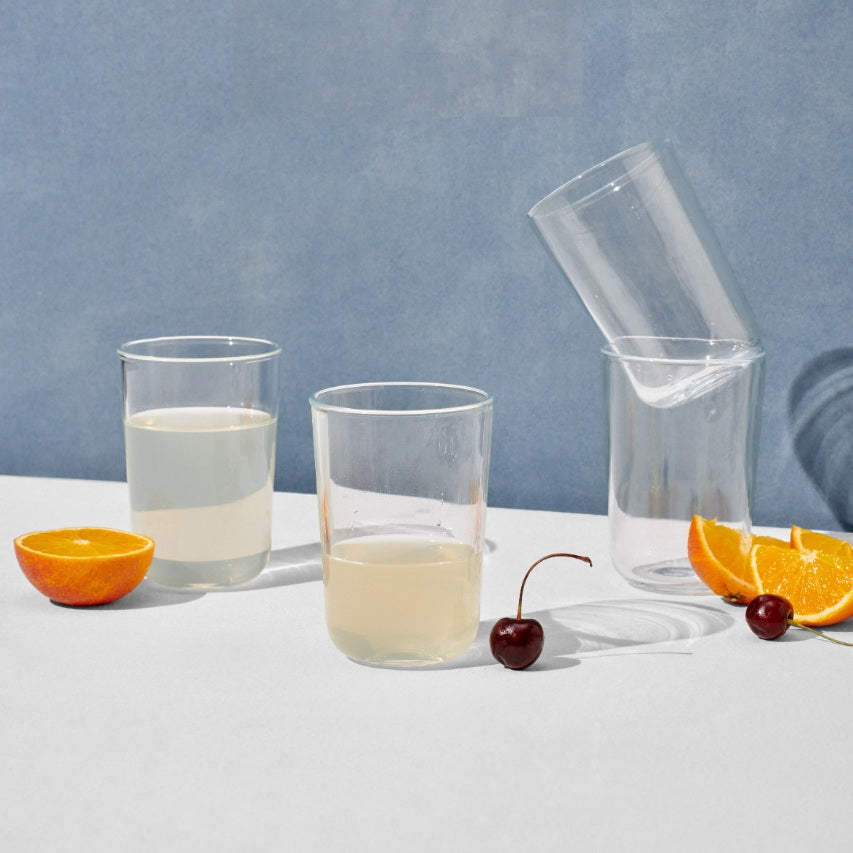 Four tall drinking glasses surrounded by cherries and orange slices