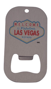 An image of a small, stainless steel bottle opener from Nuddamakers with the famous 'Welcome to Las Vegas' sign on it.