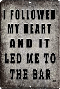 "gray funny metal sign with black writing that says ""I followed my heart and it led me to the bar"""