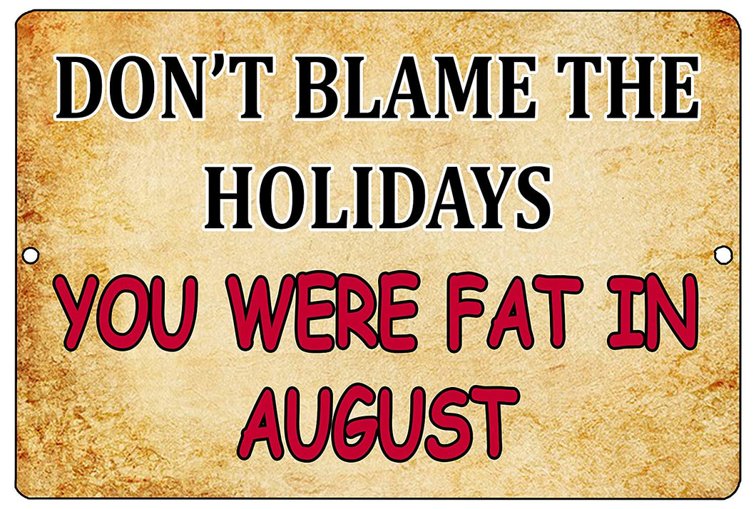 "An image of a gold funny metal sign from Nuddamakers that says ""Don't blame the holidays, you were fat in August"" in black and red writing"