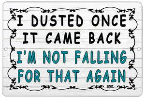 "An image of a funny metal sign from Nuddamakers with a white, wood panel background and black decoration around the edge that says ""I dusted once, it came back, I'm not falling for that again"" in black writing."