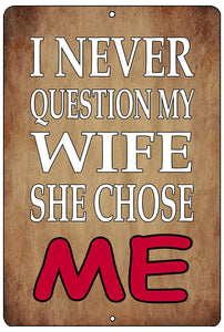 "An image of a brown funny metal sign from Nuddamakers that says ""I never question my wife, she chose me"" in white and red lettering"