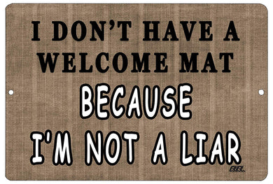 "An image of a brown funny metal sign from Nuddamakers that says ""I don't have a welcome mat because I'm not a liar"" in black and white lettering."
