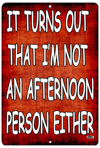 "An image of a red funny metal sign from Nuddamakers that says ""It turns out that I'm not an afternoon person either"" in white writing."